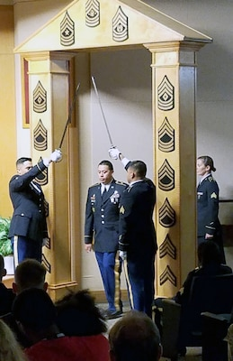 Soldiers participate in a non-commissioned officer induction ceremony Oct. 4 at Brooke Army Medical Center.  Twenty-seven Soldiers recited the NCO charge led by BAMC Command Sgt. Maj. Diamond Hough before walking through the NCO arch.