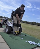 Anthony Netto, Stand Up and Play Foundation founder, takes aim before striking a golf ball at Joint Base Andrews, Md., Oct. 6, 2017. The demonstration was part of National Disability Employment Awareness Month, a time set aside in the U.S. to affirm and recognize the many contributions of American workers with disabilities.