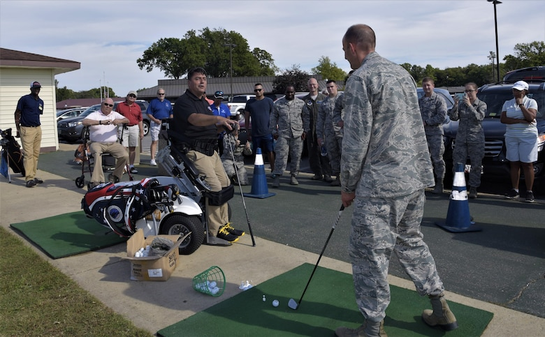 Col. E. John Teichert, right, 11th Wing and Joint Base Andrews commander, receives coaching from Anthony Netto, Stand Up and Play Foundation founder, at Joint Base Andrews, Md., Oct. 6, 2017. Netto came to JBA to demonstrate how to golf while secured to a wheelchair specially designed to enable paralyzed persons to stand up.