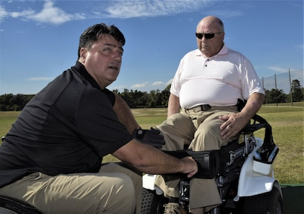 Anthony Netto, left, Stand Up and Play Foundation founder, secures Hon. John Farley, four-time Bronze Star recipient and Vietnam War veteran, into a Paramobile golf cart at Joint Base Andrew, Md., Oct. 6, 2017. Farley is a lower-limb amputee resulting from an injury he sustained in combat. The Paramobile is a specially designed wheelchair that enables paralyzed persons to stand up for activities such as swinging a golf club.