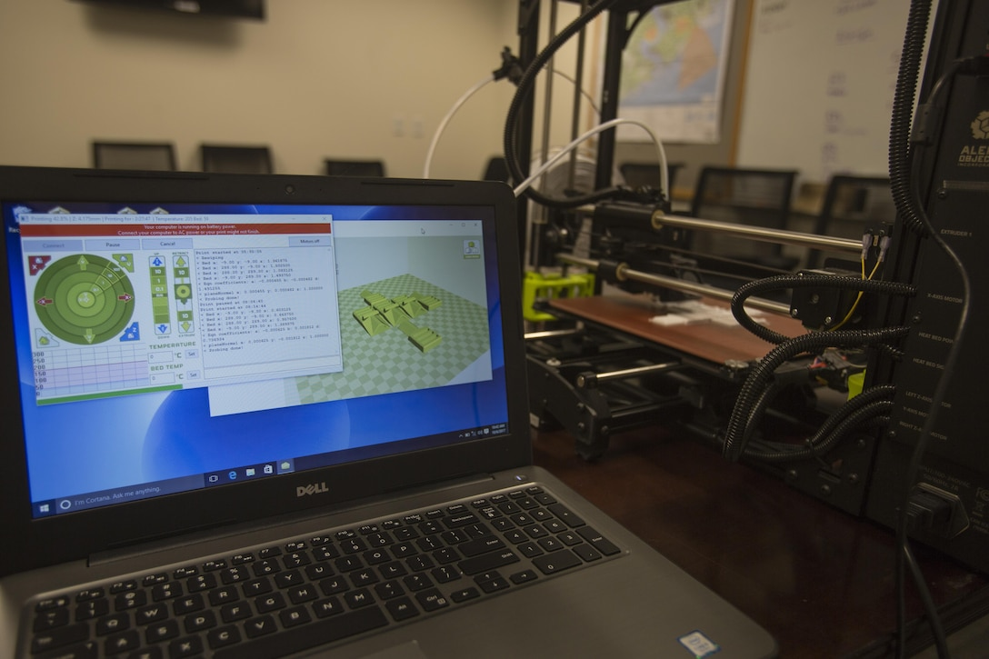 The 3-D printer from 2nd Battalion, 8th Marine Regiment is connected to a laptop with software and layouts needed to make pack clips at Camp Lejeune, N.C., Oct. 6, 2017. 2/8 is the first infantry battalion in the United States Marine Corps to utilize a 3-D printer to ensure battalion readiness in the event of equipment malfunctions. (U.S. Marine Corps photo by Lance Cpl. Ashley McLaughlin)