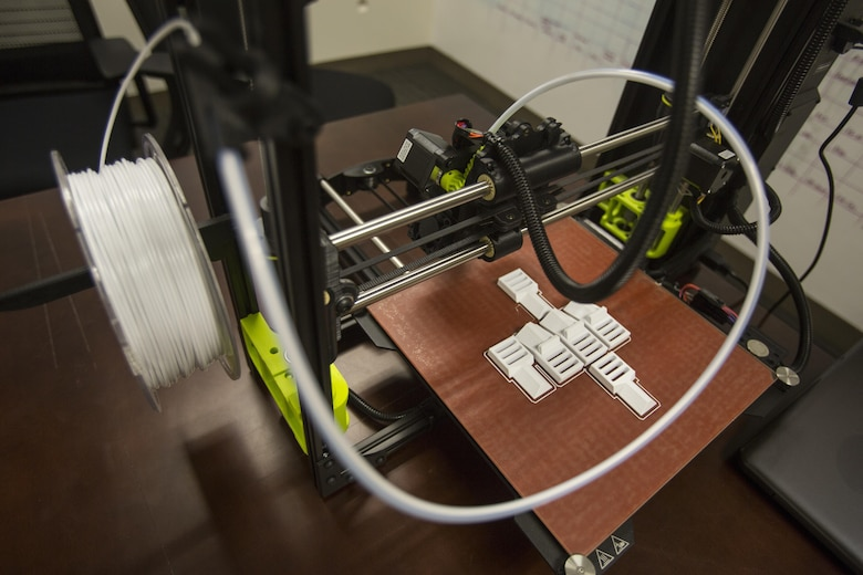 The 3-D printer and the finished layout of pack clips from 2nd Battalion, 8th Marine Regiment at Camp Lejeune, N.C., Oct. 6, 2017. 2/8 is the first infantry battalion in the United States Marine Corps to utilize a 3-D printer to ensure battalion readiness in the event of equipment malfunctions. (U.S. Marine Corps photo by Lance Cpl. Ashley McLaughlin)