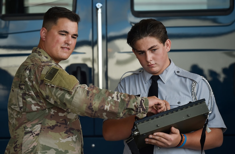 Senior Airman Matthew Reames, left, 628th Civil Engineer Squadron explosive ordnance disposal technician, shows Robert Snelson, St. Johns High School Army Junior Reserve Officer Training Corps member, how to operate an F6 robot during Joint Base Charleston's annual Career Day here Oct. 11, in South Carolina. Junior ROTC units attended Career Day to get a closer look at what it's like to serve in the U.S. Military. Career Day is a way for the base to connect with young, and possible future service members in the community. Approximately 250 Junior ROTC cadets had the opportunity to have a face-to-face interaction with service members representing the U.S. Army, U.S. Marine Corps, U.S. Navy, U.S. Air Force and U.S. Coast Guard.