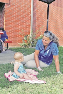 Terri Seaman, right, contract manager at the Fort Riley Post Library, plays with 7-month-old Isabella Creek, daughter of Spc. Caleb Creek a Trooper for the Commanding General's Mounted Color Guard, during a Fort Riley Post Library party Sept. 9. Seaman, who has been working at the library since 1999, helped increase patronage there with story time, movie night and parties because she said she wants everyone to feel comfortable at the library.
