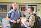 Police officer Travis Morris from Mission Police Department, Mission, Kansas, listens to queries from Spc. Sudip Guimine, 24th Composite Truck Company, 541st Combat Sustainment Support Battalion, 1st Infantry Division Sustainment Brigade, during the Army Community Service job fair Sept. 14.