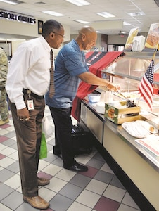 Warren Scipio, left, with the Fort Riley Mission Training Complex, waits for retired Chief Warrant Officer 4 Julius Thomas, regional sales manager for strategic culinary innovations, to provide him a serving of food during an Appreciation Food Show at Cantigny Dining Facility Sept. 12.