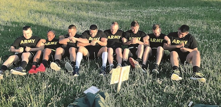Members of the 526th Quartermaster Composite Supply Company, 1st Infantry Division Sustainment Brigade, complete the team sit-up challenge at one station during unit physical training designed by Capt. Kristy Koontz, Behavioral Health Officer, 1st Sust. Bde., July 13 at Whitside Gym's track and field on Fort Riley.
