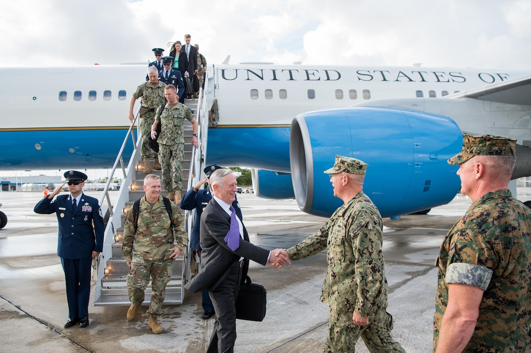 Defense Secretary Jim Mattis shakes hands with a service member on a flightline.