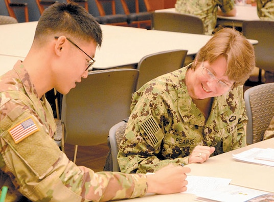 Capt. Lisa Pearse, M.D., director of Global Health Engagement, Navy Environmental and Preventative Medicine Unit Six, discusses details of a disaster response planning culmination exercise with U.S. Army Soldier.