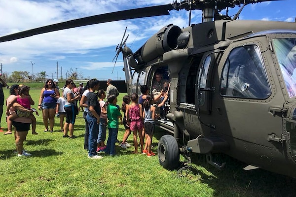 Soldiers and residents unload relief supplies from a helicopter.