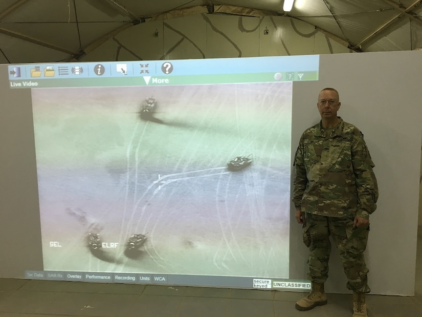 Solider stands in front of projection screen.