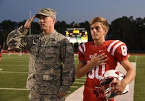 Col. C. Mike Smith, 81st Training Wing vice commander, and his son, Mac Smith, pay respect during the nation anthem at a Biloxi High School military appreciation night football game Sept. 29, 2017, in Biloxi, Miss. Smith, along with other Keesler Air Force Base leadership, participated in the coin toss to determine which team would receive the ball first. (U.S. Air Force photo by Kemberly Groue)