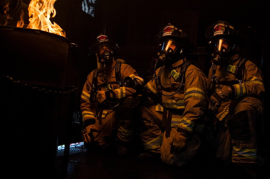 Senior Airman Robert Jones, left, Airman 1st Class Nicholas Jarnecke, center, and Airman 1st Class Tyler Jones, right, all 52nd Civil Engineer Squadron firefighters, experience a rollover fire inside a burn house trailer at Spangdahlem Air Base, Germany, Oct. 5, 2017. Rollover fires happen when fire gasses rise in an enclosed area, collect on the ceiling and ignite. (U.S. Air Force photo by Senior Airman Preston Cherry)