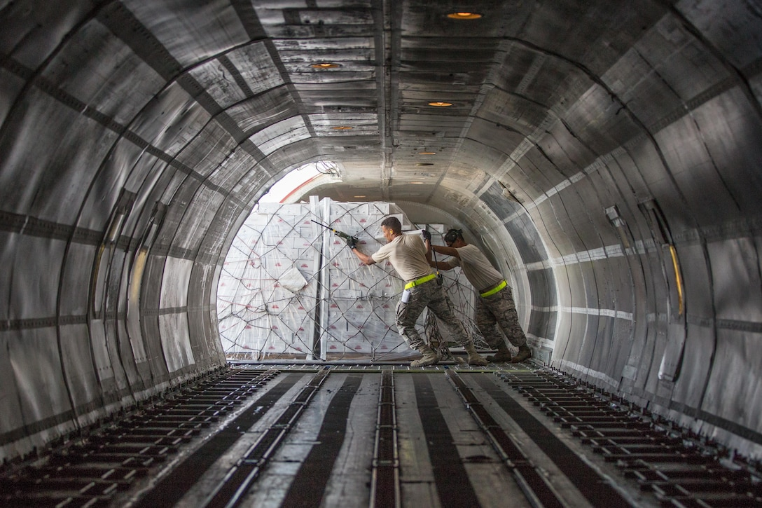 Senior Airman Terrance Thomas (left) and Master Sgt. Frank Ingles, both assigned to 821st Contingency Response Squadron, unload pallets of food from a 727 commercial airliner at Rafael Hernandez Airport, Aguadilla, Puerto Rico, Oct. 9, 2017. The airliner carried 52,600 pounds of food and water intended for distribution to the residents of Aguadilla, Arecido, Ponce, Utuado and the surrounding neighborhoods. (U.S. Army photo by Staff Sgt. Pablo N. Piedra)