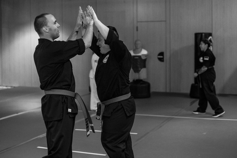 U.S. Air Force Staff Sgt. Brandon Sabin, 86th Airlift Wing Public Affairs broadcast journalist, and U.S. Army Staff Sgt. Michael Decker, clap hands after practicing a form during a mixed martial arts class at the Vogelweh Community Center on Vogelweh Military Complex, Germany, Oct. 11, 2017. Sabin explained, in martial arts everyone wants each other to succeed so they work together to help each person grow. (U.S. Air Force photo by Senior Airman Devin Boyer)