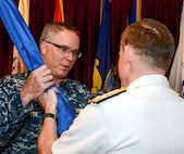 Navy Rear Adm. T. J. White, left, takes the unit colors from Adm. Michael S. Rogers, Commander, USCYBERCOM, to become the third commander of the Cyber National Mission Force. The CNMF plans, directs and synchronizes full-spectrum cyberspace operations to deter, disrupt, and if necessary, defeat adversary cyber actors to defend the nation.