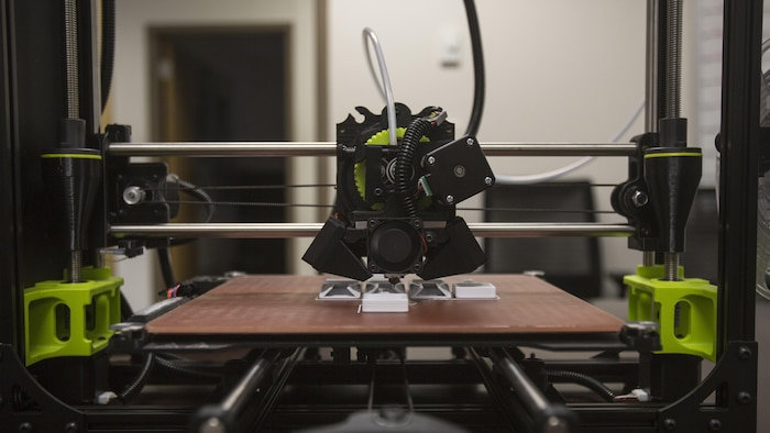The 3-D printer from 2nd Battalion, 8th Marine Regiment begins to form the base layer of pack clips