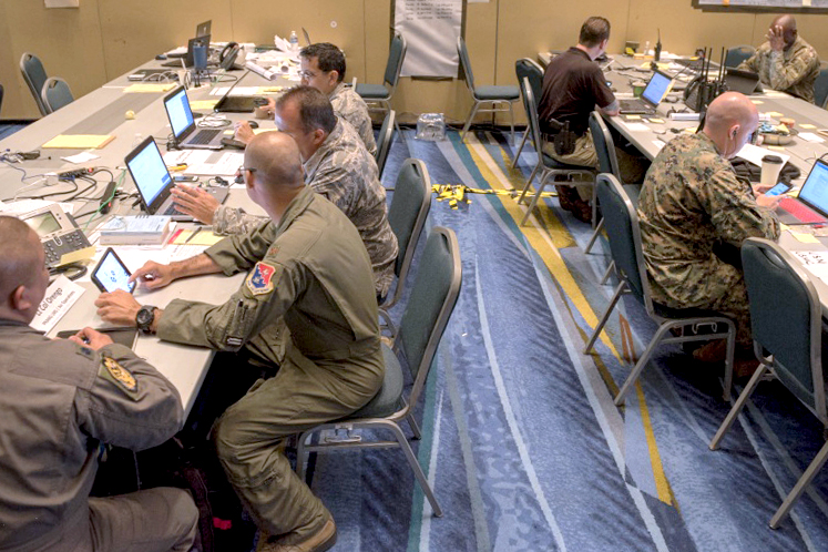 Lines of people and service members sit at tables and look at papers and laptops.