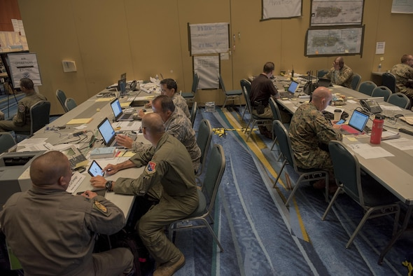 Airmen work with representatives of other agencies in a hurricane relief coordination center.