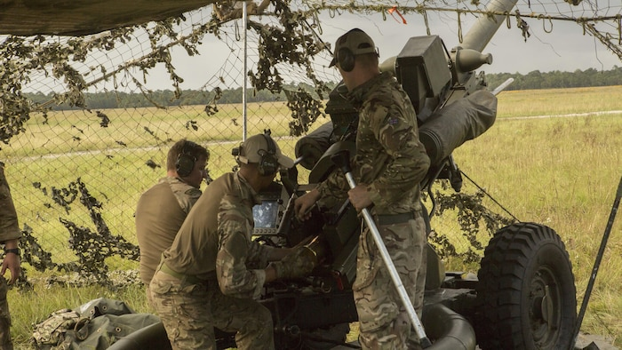 British commando gunners prepare 105mm shells to be fired from an M119A3 Howitzer during field artillery training at Camp Lejeune, N.C., Oct. 11, 2017.