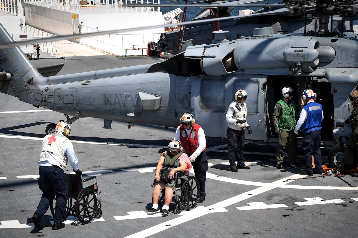 A sailor pushes a person in a wheelchair away from a helicopter.