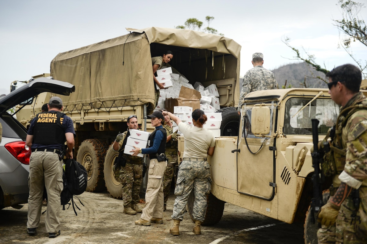 A group of people unload boxes from the back of a military vehicle.