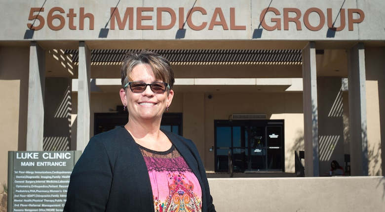 "Melissa Kunkel, 56th Dental Squadron expanded function dental assistant, stands in front of the 56th Medical Group at Luke Air Force Base, Ariz., Sept 27, 2017. Kunkel earned the Air Force Medical Service's August ""Trusted Care Hero"" award for a discovery she made in the dental squadron. (U.S. Air Force photo/SSgt Jensen Stidham)"
