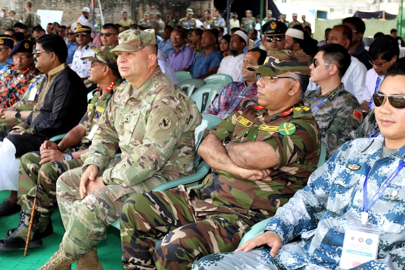 An audience of seated military members and civilians look forward.