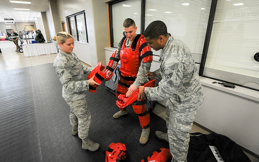 Airman 1st Class Sarah Sillitoe and Senior Airman Jasson Adamson, 14th Security Forces Squadron unit trainers, assist Airman 1st Class Ian Bennett, 14th SFS installation entry controller, with a RedMan suit Oct. 3, 2017, during the Imagine the Possibilities Career Expo at the BancorpSouth Arena in Tupelo, Mississippi. Airmen from the 14th SFS showcased law enforcement capabilities that are available through the Air Force. The expo was from Oct. 3-5 and had more than 7,000 eighth grade students from schools throughout 17 northeast Mississippi counties attend. Airmen from Columbus Air Force Base, Mississippi, represented 21 careers available in the Air Force. (U.S. Air Force photo by Staff Sgt. Christopher Gross)