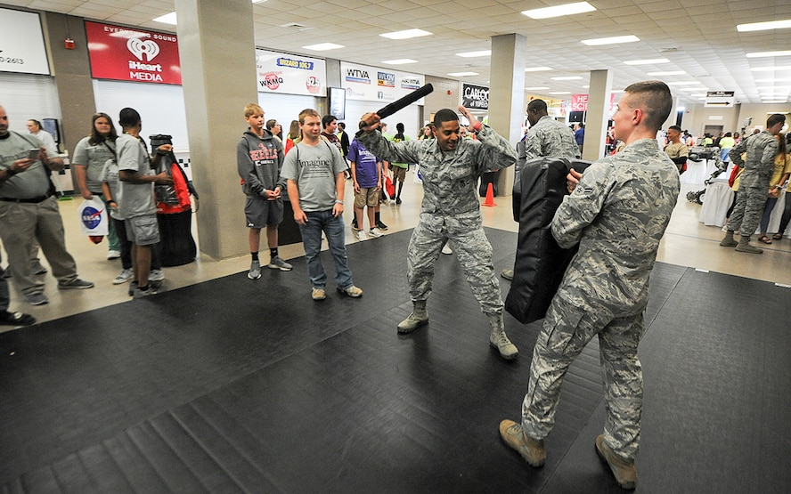 Senior Airman Jasson Adamson, 14th Security Forces Squadron unit trainer, shows a student how to use a baton while protecting themselves and what instructions should be given to have an individual comply Oct. 3, 2017, during the Imagine the Possibilities Career Expo at the BancorpSouth Arena in Tupelo, Mississippi. Airmen from the 14th SFS also had several weapons on display and had several military working dog demonstrations throughout the three days. (U.S. Air Force photo by Staff Sgt. Christopher Gross)