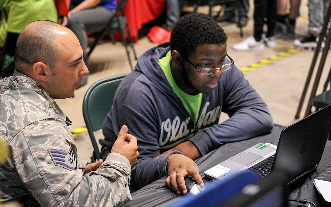 Tech. Sgt. Henry Schultz, 14th Logistics Readiness Squadron NCO in Charge of Logistics Plans, helps a student use ICODES software on a computer Oct. 3, 2017, during the Imagine the Possibilities Career Expo at the BancorpSouth Arena in Tupelo, Mississippi. The software is used to help find the center of balance on an aircraft. (U.S. Air Force photo by Staff Sgt. Christopher Gross)