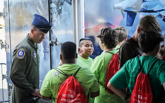 Col. Douglas Gosney, 14th Flying Training Wing Commander, talks to students as they wait in line for the Rapid Strike simulator Oct. 3, 2017, during the Imagine the Possibilities Career Expo at the BancorpSouth Arena in Tupelo, Mississippi. Airmen from Columbus AFB represented seven pathways at the expo, including aerospace, communications, engineering, government and public administration, health sciences, logistics and law and public safety. (U.S. Air Force photo by Staff Sgt. Christopher Gross)