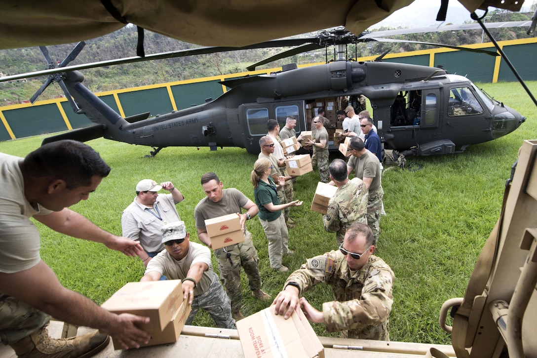 Two lines of people unload boxes from a helicopter.