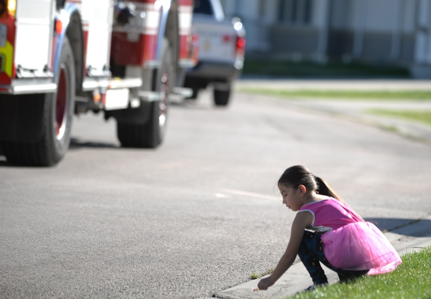 Emmalyn Jensen, daughter of Staff Sgt. Michael Jensen, a cyber transport systems technician assigned to the 28th Communications Squadron, picks up candy on the side of the road during the Fire Prevention Week Parade at Ellsworth Air Force Base, S.D., Oct. 7, 2017. Members of the Ellsworth community came out to participate in the parade and raise awareness for fire prevention. (U.S. Air Force photo by Airman 1st Class Thomas Karol)