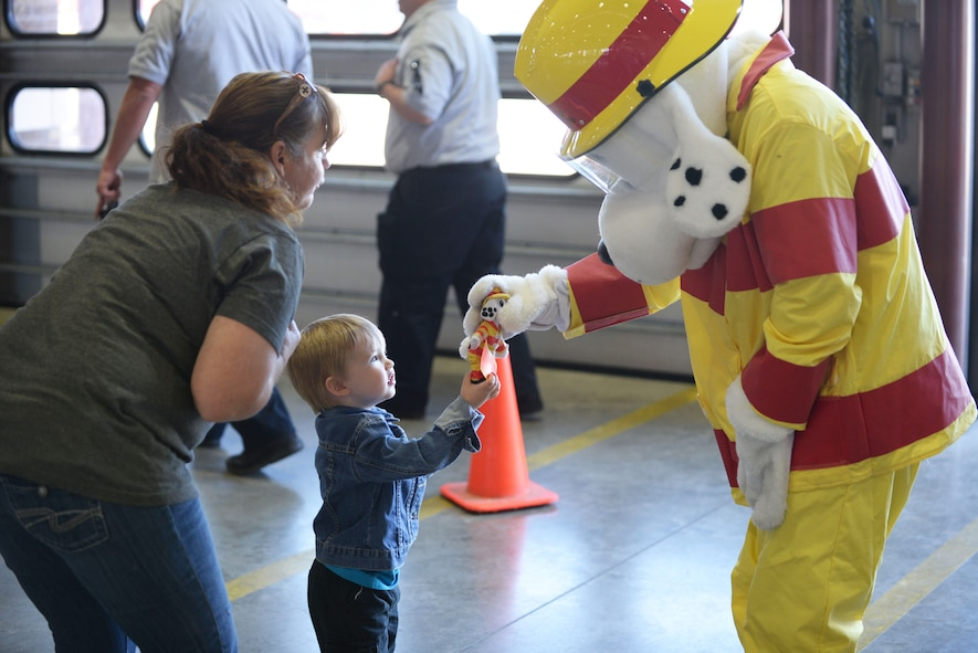 A child gives Sparky the Fire Dog, the mascot of the 28th Civil Engineer Squadron Fire Protection Flight, a toy identical to himself at Ellsworth Air Force Base, S.D., Oct. 7, 2017. The 28th CES Fire Protection Flight hosted an open house for the local community and kicked off National Fire Prevention Week by raising awareness about fire safety. (U.S. Air Force photo by Airman 1st Class Thomas Karol)