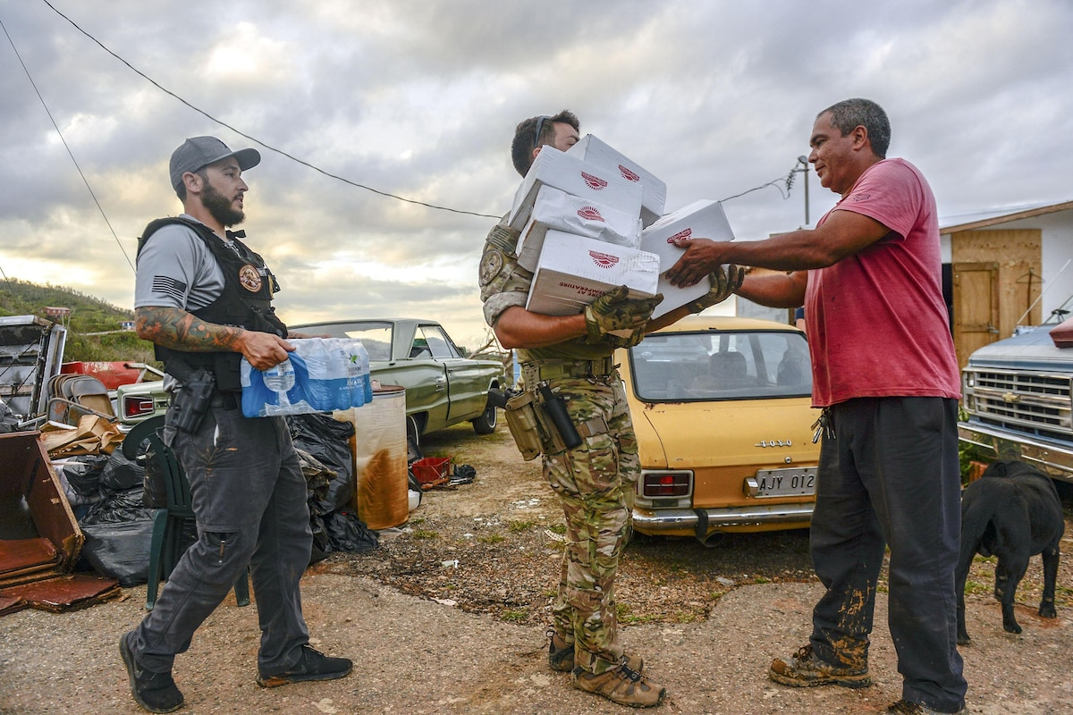 A man passes cardboard boxes to another man, while a third holds a case of water.