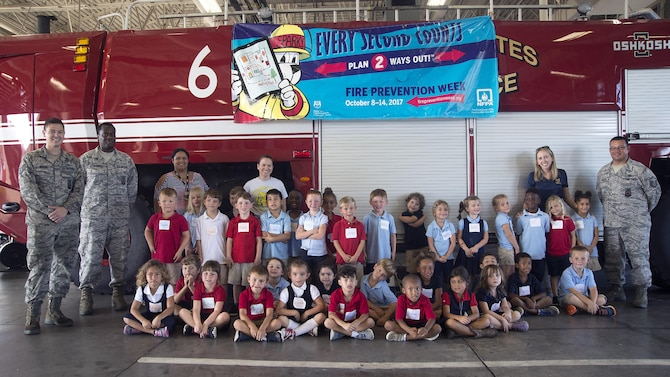 MacDill firefighters pause for a photo celebrating Fire Prevention Week with students from Tinker K-8 School at MacDill Air Force Base, Fla., Oct. 10, 2017.