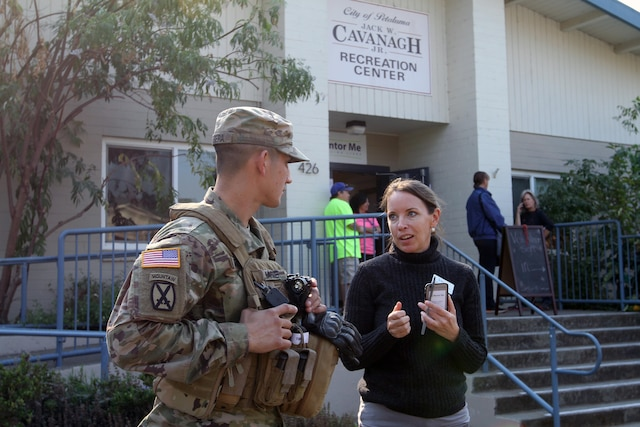 A soldier speaks to a woman in front of a building.