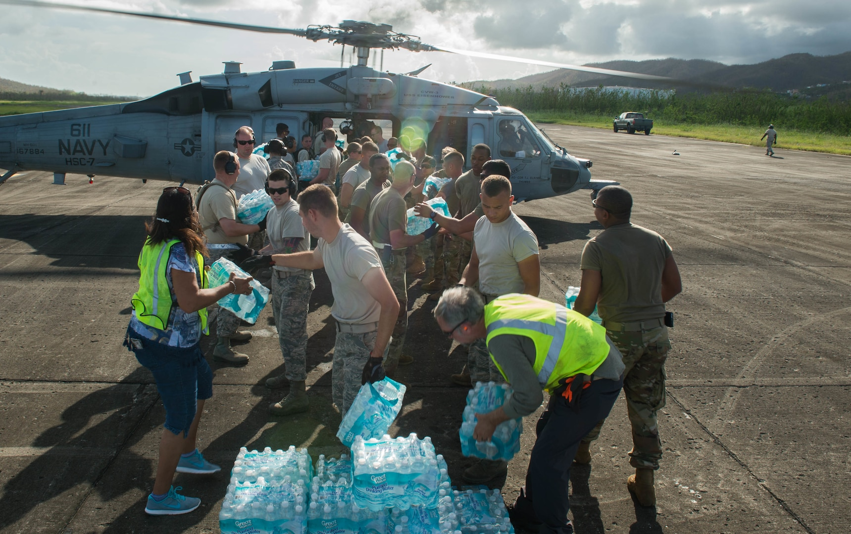 Airmen, soldiers and Federal Emergency Management Agency personnel load food and water onto a helicopter at Roosevelt Roads, Puerto Rico.