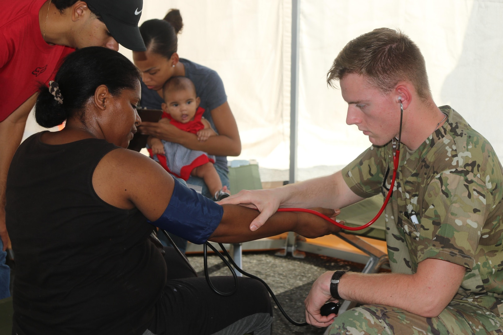 A medic with the 1st Armored Division, tends to patients near Fajardo, Puerto Rico.
