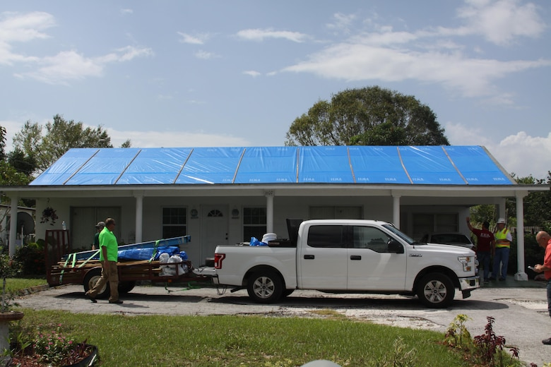 Contractors pack up materials and gear after installing fiber-reinforced plastic sheeting on a Hurricane Irma-damaged roof in Sebring, Florida Oct. 1, 2017