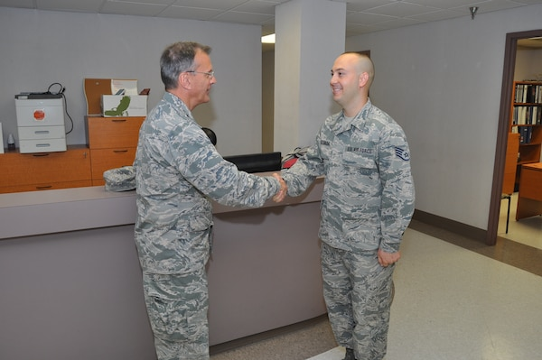 Maj. Gen. Randall Ogden, 4th Air Force commander, presents a commander's coin to Staff Sgt. Isaiah Estrada, 433rd Civil Engineer Squadron contractor, Oct. 15, 2017 for his accomplishments and achievements within the squadron. Both Gen. Ogden and Chief Master Sgt. Timothy White, Jr., 4th AF command chief, presented approximately 14 commanders coins to outstanding Reserve Citizen Airmen during their four-day visit to the 433rd Airlift Wing. (U.S. Air Force photo/Senior Airman Bryan Swink)