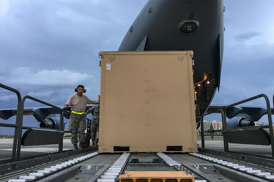 An Airman from the Kentucky Air National Guard's 123rd Contingency Response Group dowloads relief supplies from a U.S. Air Force C-17 aircraft at Luis Muñoz Marín International Airport in San Juan, Puerto Rico, in the wake of Hurricane Maria Oct. 5, 2017. The unit's Airmen established an aerial port of debarkation upon arrival here Sept. 23, and have processed more than 7.2 million pounds of cargo and humanitarian aid for distribution in the first three weeks of the operation. (U.S. Air National Guard photo by Lt. Col. Dale Greer)