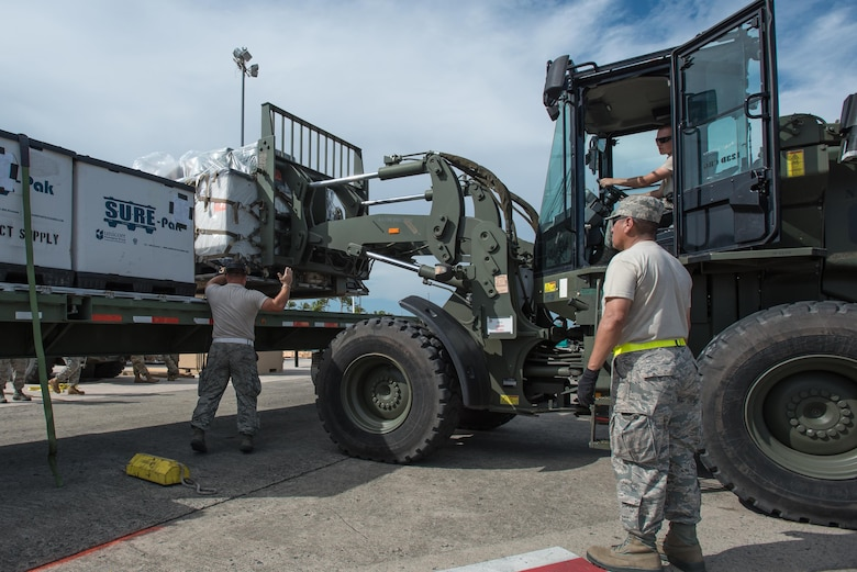 Airmen from the Kentucky Air National Guard's 123rd Contingency Response Group, augmented by troops from the active-duty Air Force and Air National Guard units in multiple states, load relief supplies onto trucks for distribution at Luis Muñoz Marín International Airport in San Juan, Puerto Rico, in the wake of Hurricane Maria Oct. 6, 2017. The unit's Airmen established an aerial port of debarkation upon arrival here Sept. 23, and have processed more than 7.2 million pounds of cargo and humanitarian aid for distribution in the first three weeks of the operation. (U.S. Air National Guard photo by Lt. Col. Dale Greer)