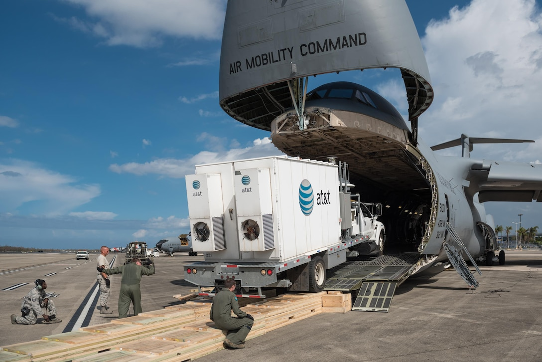Members of the Kentucky Air National Guard's 123rd Contingency Response Group, augmented by Airmen from the active-duty Air Force and Air National Guard units in multiple states, download a mobile cell-phone tower truck from a U.S. Air Force C-5 Galaxy at Luis Muñoz Marín International Airport in San Juan, Puerto Rico, in the wake of Hurricane Maria Oct. 6, 2017. The truck will be used to help restore cell-phone service on the island. (U.S. Air National Guard photo by Lt. Col. Dale Greer)
