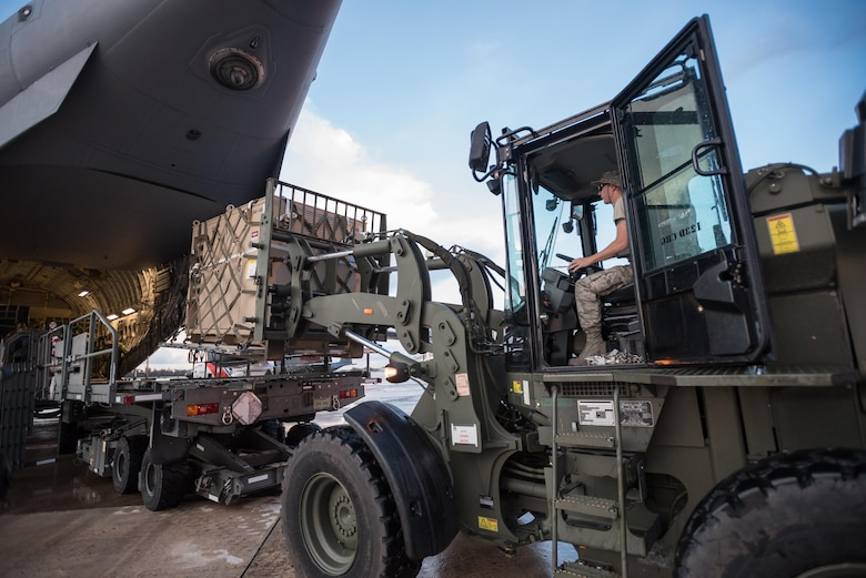 Airmen from the Kentucky Air National Guard's 123rd Contingency Response Group, augmented by troops from the active-duty Air Force and Air National Guard units in multiple states, dowload relief supplies from aircraft around the clock at Luis Muñoz Marín International Airport in San Juan, Puerto Rico, in the wake of Hurricane Maria Oct. 6, 2017. The unit's Airmen established an aerial port of debarkation upon arrival here Sept. 23, and have processed more than 7.2 million pounds of cargo and humanitarian aid for distribution in the first three weeks of the operation. (U.S. Air National Guard photo by Lt. Col. Dale Greer)