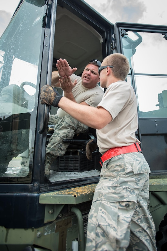 Staff Sgt. John May, an aerial porter from the Kentucky Air National Guard's 123rd Contingency Response Group, discusses cargo handling with another aerial porter Oct. 7, 2017, at Luis Muñoz Marín International Airport in San Juan, Puerto Rico. May's unit has processed more than 7.2 million pounds of humanitarian aid here since arriving Sept. 23 in the wake of Hurricane Maria. (U.S. Air National Guard photo by Lt. Col. Dale Greer)
