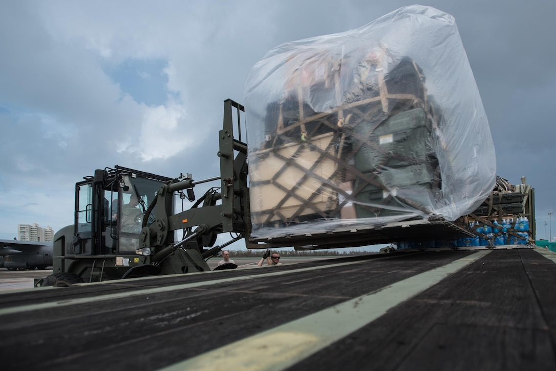 Airmen from the Kentucky Air National Guard's 123rd Contingency Response Group, augmented by troops from the active-duty Air Force and Air National Guard units in multiple states, load relief supplies onto trucks for distribution at Luis Muñoz Marín International Airport in San Juan, Puerto Rico, in the wake of Hurricane Maria Oct. 7, 2017. The unit's Airmen established an aerial port of debarkation upon arrival here Sept. 23, and have processed more than 7.2 million pounds of cargo and humanitarian aid for distribution in the first three weeks of the operation. (U.S. Air National Guard photo by Lt. Col. Dale Greer)