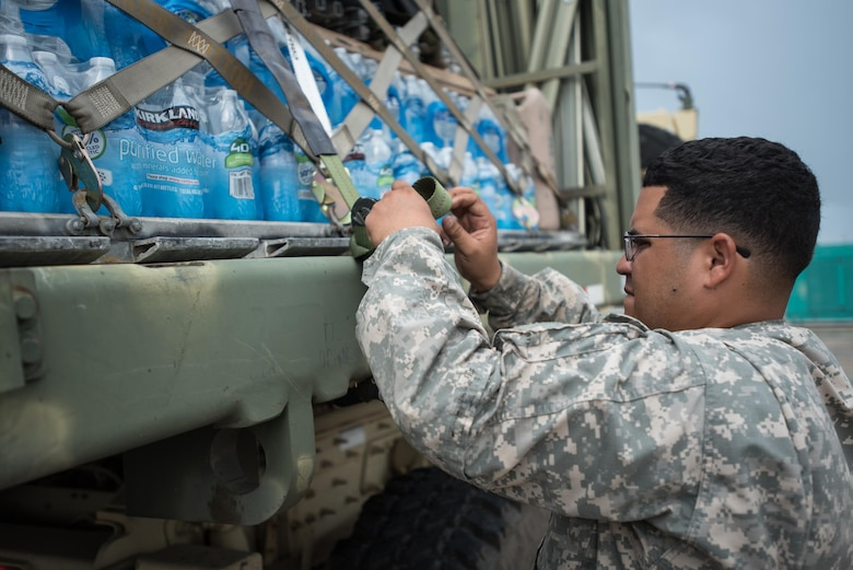 Spc. German Santiago from the Puerto Rico Army National Guard's 755th Transportation Command straps pallets of water to a flat-bed trailer at Luis Muñoz Marín International Airport in San Juan, Puerto Rico, on Oct. 7, 2017. The cargo will be used for recovery operations following Hurricane Maria. (U.S. Air National Guard photo by Lt. Col. Dale Greer)