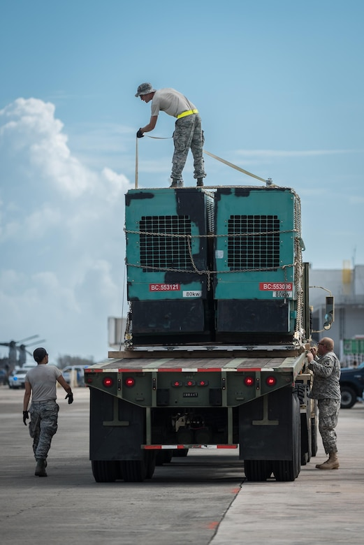 An aerial porter from the Nevada Air National Guard straps an electric generator to a flat-bed truck Oct. 7, 2017, at Luis Muñoz Marín International Airport in San Juan, Puerto Rico. The generator will be used to assist with relief operations on the island following Hurricane Maria. (U.S. Air National Guard photo by Lt. Col. Dale Greer)